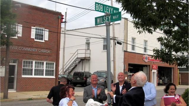 Toms River officials and WOBM radio host Bob Levy's family and friends gathered on Robbins Street for the unveiling of a sign for Bob Levy Way.
