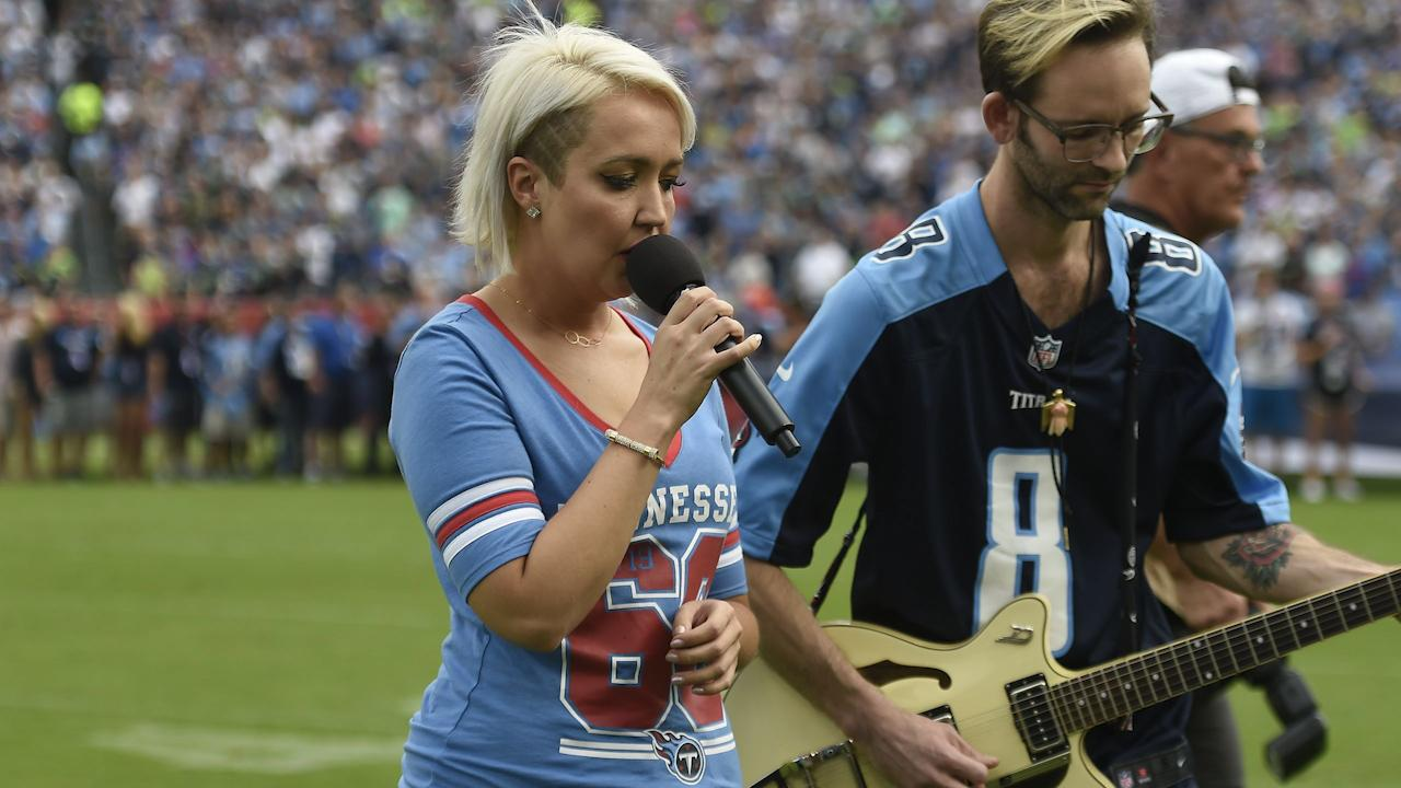 Meghan Linsey kneels after singing national anthem at Titans-Seahawks game