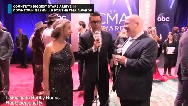 Bobby Bones gives commentary on Carrie Underwood's CMA Awards gown as she walks down the red carpet.
