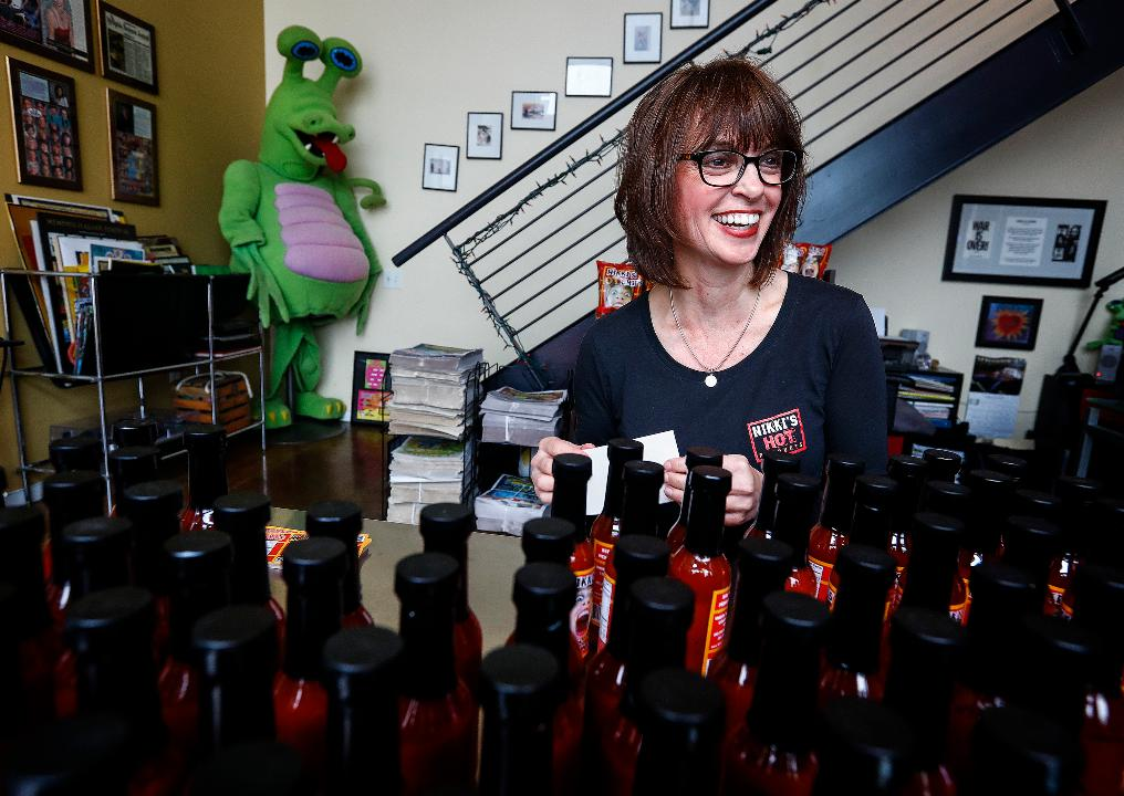 Nikki Schroeder, owner of Nikki's Hot Products places labels on her Hot Bloody Mary mix Monday afternoon. Schroeder uses Pick Tennessee to have all her labeling made locally.