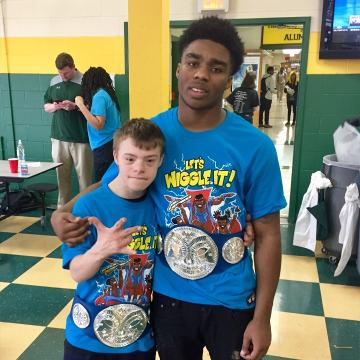 High school football star Jacob Frazier delights his friend Stephen Mast with a replica championship belt and a T-shirt from Mast's favorite tag team