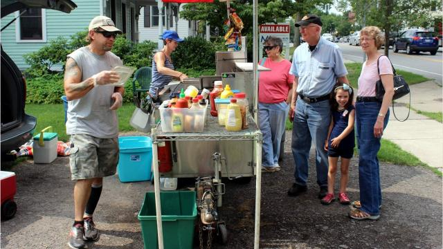 An unassuming hot dog cart, owned and operated by Charlie Clottin and his wife, Bernadette, serves people at 10 N. Main St., Pittsford.