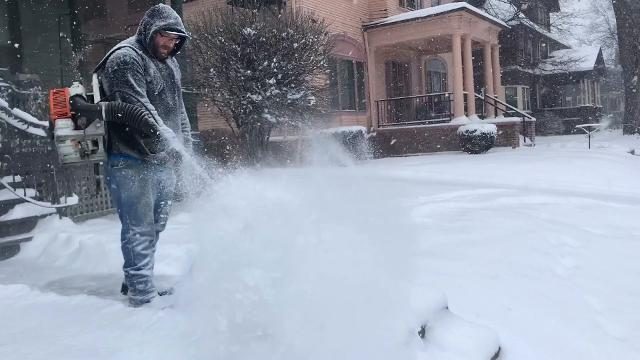 Michael Gullen of Geneseo uses a leaf blower to clear the snow from the entrance of several properties on Oxford Street during a snowstorm. This method seems to only be effective with light snow. (Jan. 30, 2018)