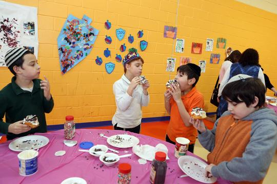 On the first day of Hanukkah students in preschool through 8th grade celebrated with crafts, decorating jelly donuts, and games during the Hanukkah expo at The Hebrew Academy in New City.