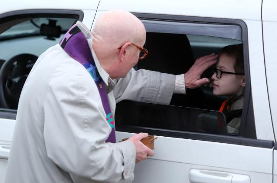The Rev. Daniel Ramm distributes ashes on Ash Wednesday at Hawthorne Reformed Church Feb. 14, 2018 for commuters short on time.