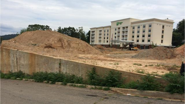 Will concrete wall in front of Holiday Inn come down? What happened to Reed Street sidewalks?