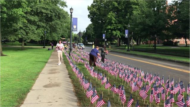 Students and faculty members at Elmira College place nearly 3,000 American flags along Park Place on Tuesday to honor the nearly 3,000 people who died in the Sept. 11, 2001 terrorist attacks.