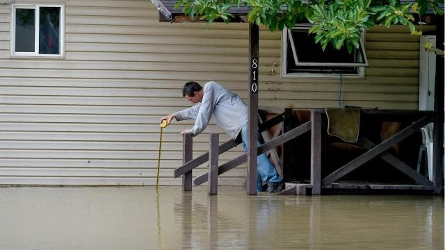 Mark Barber of Candor woke to flood waters from Catatonk Creek in the front yard of his rental home. Barber and his wife evacuated their three young children and he spent much of the rest of the morning monitoring the water as it inched higher.
