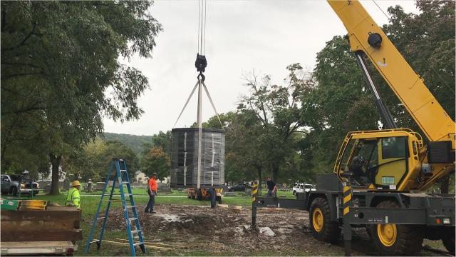 A crane positions a new 9-ton columbarium on a platform at Woodlawn Cemetery in Elmira.