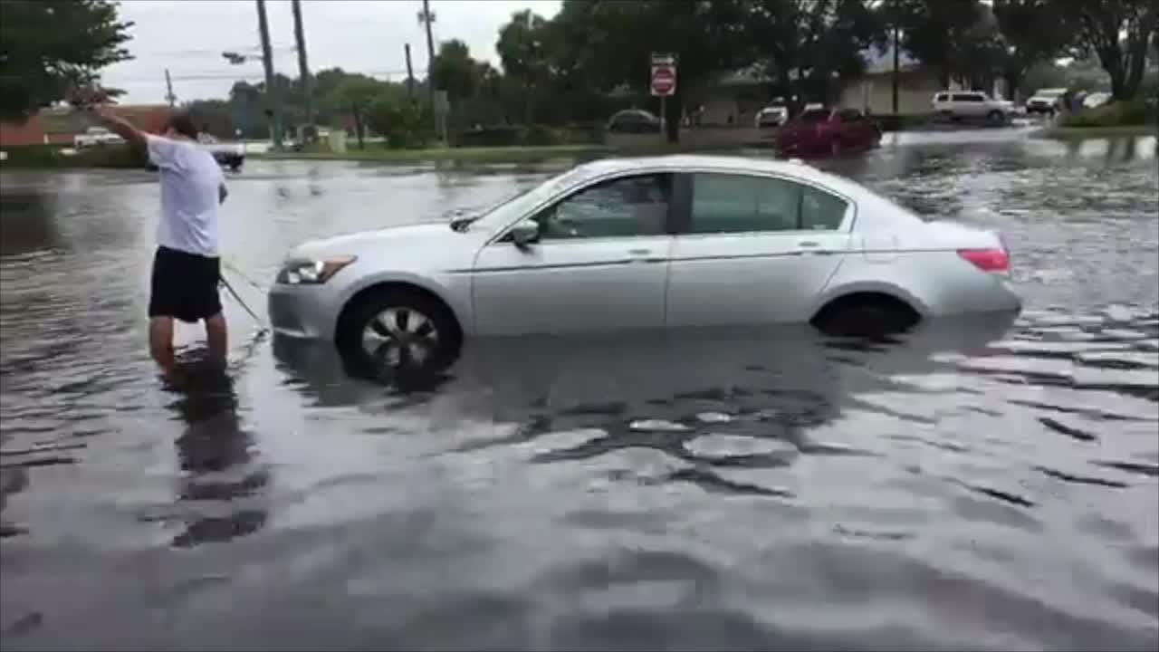 Video: 2 help pull car out of flooded waters