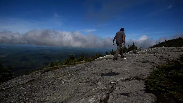 Adam Joseph of the Green Mountain Club greets people on top of Mount Mansfield on Friday, July 28, 2017, and advises on where to step -- and not.