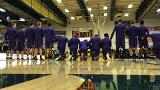 St. Michael's College men's basketball team members kneel during the national anthem