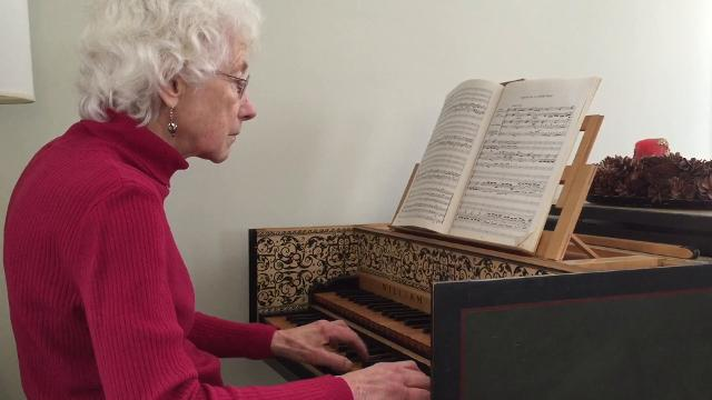 Elizabeth Metcalfe, co-founder of The Oriana Singers, plays a few seconds of a Handel organ concerto on the harpsichord in her Burlington home.