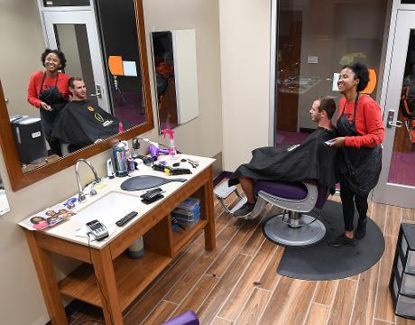 Tyler Barton turned a chance meeting with Clemson coach Dabo Swinney into her dream career as the hair care specialist at the barber shop inside the Reeves Football Complex
