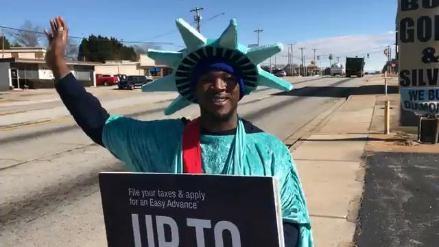 Daecwon Bruster, 23, waves at motorists passing by on U.S. 123 in Easley, attracting attention for Liberty Tax Service.