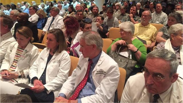 Doctors in white Greenville Health System coats crowded into the Greenville County Council chambers Tuesday night to urge local leaders to drop support for a sale of the nonprofit system.