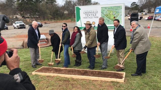 Officials of the Greenville Revitalization Corporation and the Greenville Textile Heritage Society break ground outside the former Monaghan Mill for a park honoring the city's textile history.