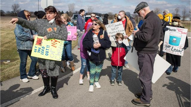 Nearly 30 citizens— some with disposable dustmasks strapped on their faces —marched down Mount Pleasant Boulevard in front of the plant where millions of lead batteries are recycled every year.