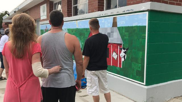 On Wednesday night, the community got its first look at the completed mural, which spans an entire side of the old pool house in the city park, flanking the Spray Park.
