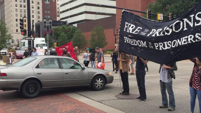 Protesters briefly shut down a major thoroughfare in downtown Lansing to protest the U.S. prison system.