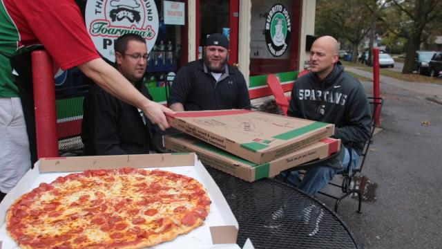 LSJ sportswriter Cody Tucker chats with former MSU football players Ryan Van Dyke and Todd Acchione about the MSU vs. UM matchup while the three attempt a 24-inch pizza challenge at Toarmina's Pizza in Ann Arbor.