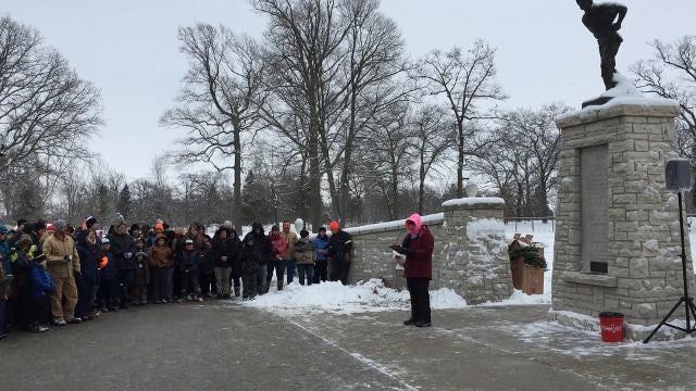 People honor veterans by placing wreaths at cemeteries