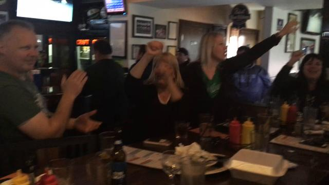 Fans celebrate by singing the Michigan State fight song at Steakhouse Philly Bar & Grill in Lansing after it completed the biggest comeback in Big Ten history on Feb. 18, 2018, in beating Northwestern 65-60.