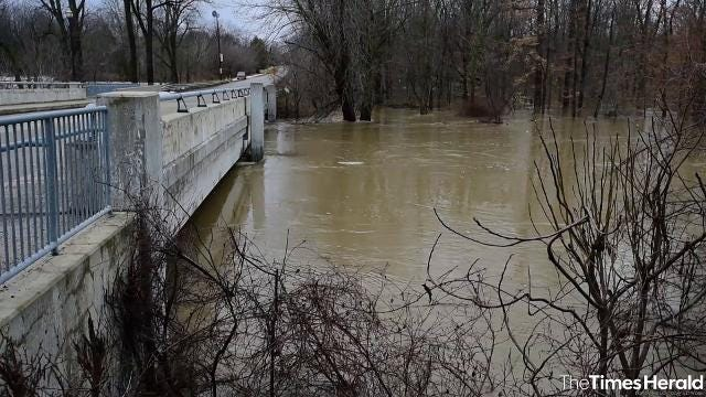 Warm temperatures and heavy rains led to high water levels on the Black River in Croswell, submerging part of the Swinging Bridge and bringing water levels to the bottom of the Harrington Road bridge.