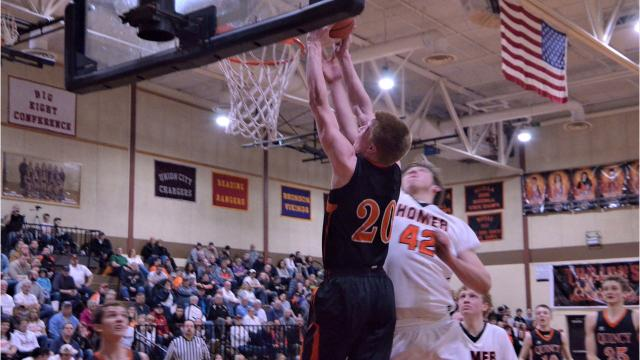 Orioles pull away for 81-67 victory over Trojans to move into first place in the Big 8 Conference standings.