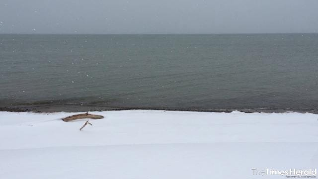 Snow falls over a calm Lake Huron Wednesday, March 8.