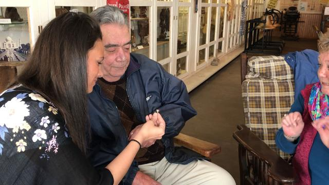 Mike O'Toole and his daughter, Michelle, receive his mother's 1929 Sunfield High School class ring on Friday, March 9, 2018, more than 30 years after it was discovered in the gravel outside what was once the high school.