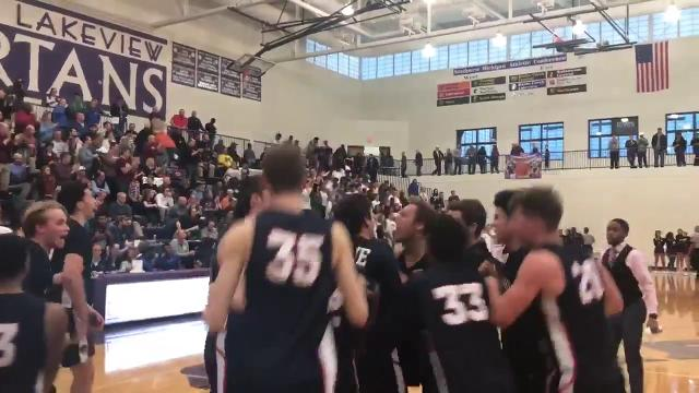 The East Lansing Trojans celebrate after their victory over Okemos.