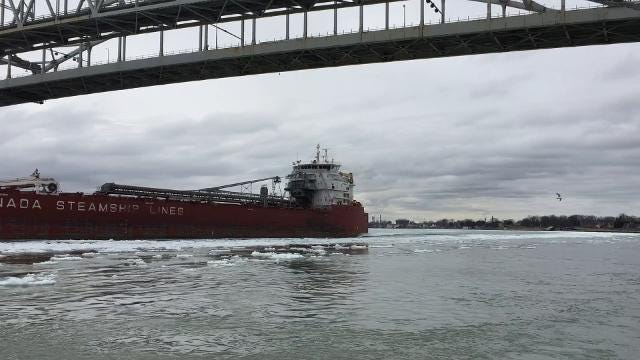 The lake freighter Thunder Bay passes under the Blue Water Bridge and into Lake Huron.