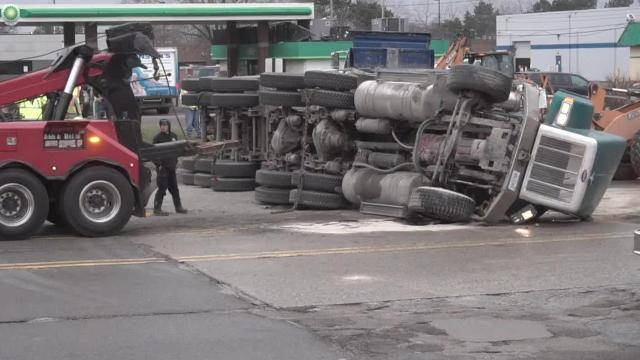 Gravel truck overturns, crews right it, truck leaves a mess.