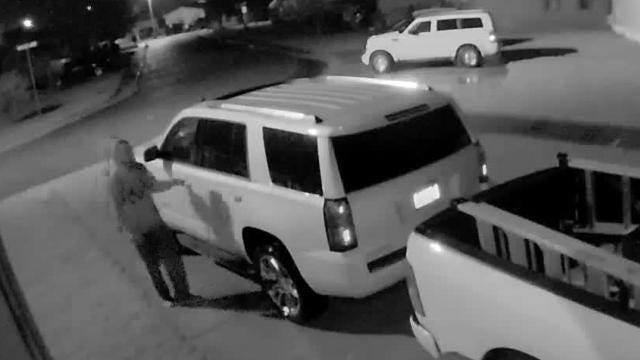 A man goes through a a vehicle in a Plymouth Township neighborhood where several vehicles were burglarized over a recent weekend. Police are asking motorists to lock their parked vehicles.