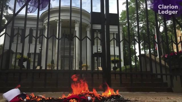 """While chanting """"no more hate in our state,"""" members of the Poor People's Campaign burned a Mississippi flag and a Confederate battle flag outside the governor's mansion on Monday."""