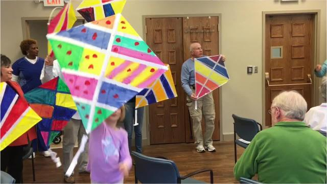 The Respite Ministry at Montgomery's First United Methodist Church, to end a day, sings a song. On Monday, the participants began the day by painting kites, which had dried and were shown off before everyone left.