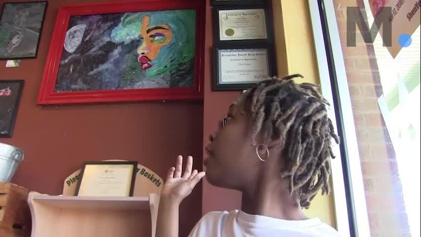 Aleah Hosea shows some of her paintings at Montgomery's Wishbone Cafe, where she is also the assistant manager, on Thursday, March 15, 2018. Several are marked for sale.