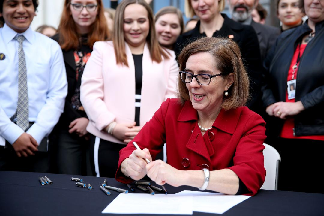 "Gov. Kate Brown signs HB 4145 at the Oregon State Capitol in Salem on Monday, March 5, 2018. The law expands the prohibition of owning a gun to people convicted of domestic violence, closing the ""intimate partner loophole"" and blocks people convicted"