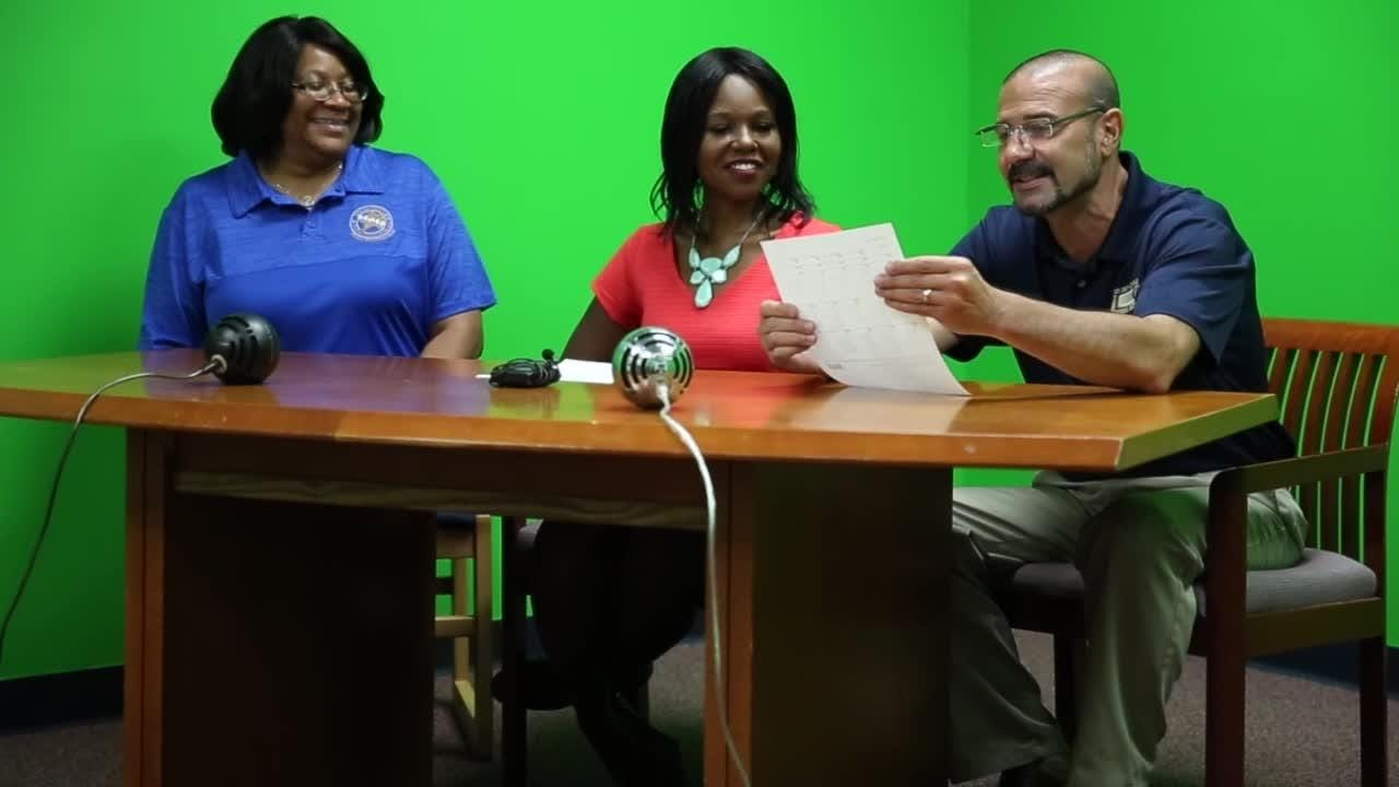 Superintendent Rocky Hanna reads the first day of school lunch menu on the Apalachee Elementary School morning news with Apalachee Principal Iris Wilson (left) and WCTV's Lanetra Bennett August 14.