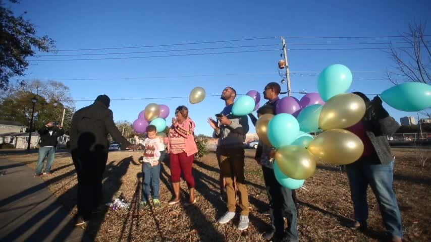 Vanessa Henry gathers her family at Carter-Howell-Strong Park Friday to release balloons as a tribute for her niece, Tiffany Nance, who was killed one year ago.