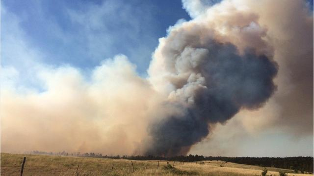 A fire on the Pine Ridge Indian Reservation is burning thousands of acres and has damaged two structures.