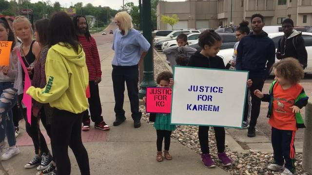 More than a dozen people gathered Monday afternoon in front of the Minnehaha County Administration building in downtown Sioux Falls.