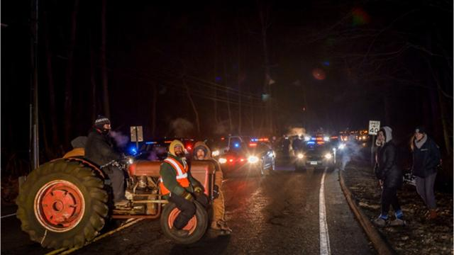 Four New York residentswere arrested Tuesday night after Connecticut State Police said they chained themselves to a tractor in the middle of Route 55 in New Milford, Connecticut.