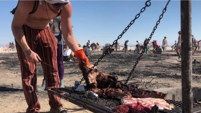 A camp who wants people to face their food, cooked whole pig and lamb on remnants of the man