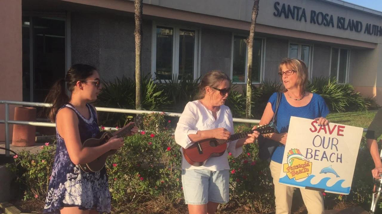 Protesters against a U.S. Senate bill to change beach ownership greet Escambia County Commissioner Grover Robinson with a protest song.