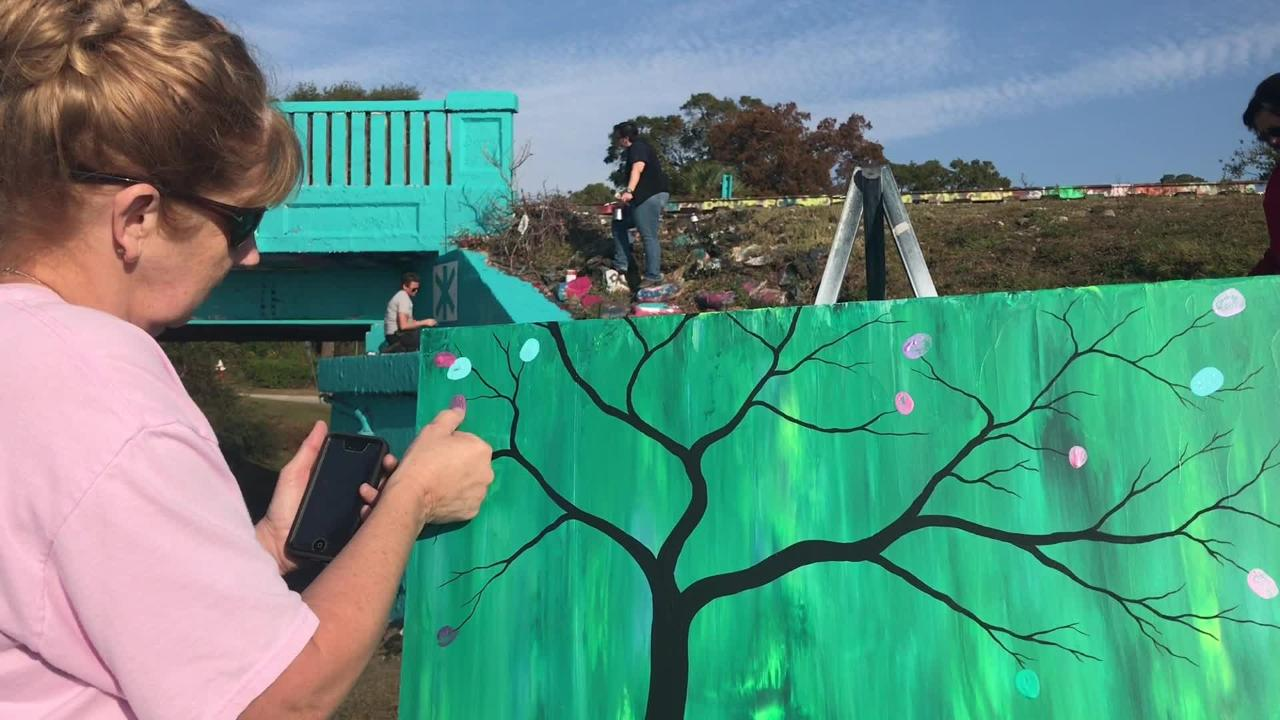 After paramedic and trainer Kara Zaremba died of ovarian cancer, a group of her friends and colleagues painted the graffiti bridge in her honor Sunday.