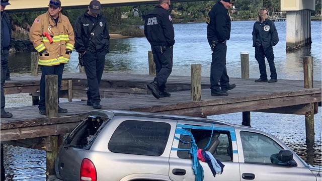 First responders investigated a silver Dodge Durango that was found almost completely submerged at the Navy Point Boat Ramp on Friday morning. (Annie Blanks/ablanks@pnj.com)