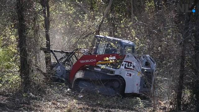Machinery clears brush from site of former homeless camp