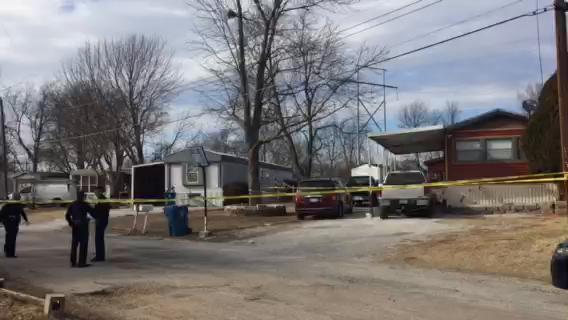 Crime scene tape was set up around a light gray trailer home.